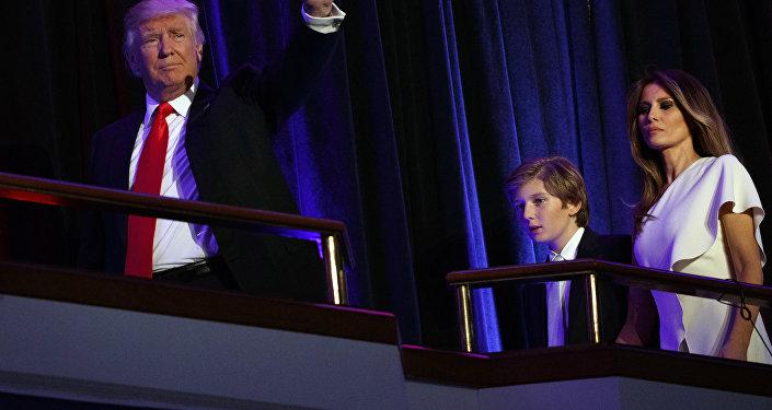 El presidente electo Donald Trump camina con su hijo Barron y su esposa Melania