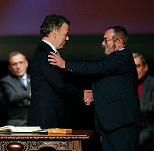 Presidente de Colombia, Juan Manuel Santos, y máximo líder de las FARC, Rodrigo Londoño Echeverri, alias 'Timochenko', firman el nuevo acuerdo de paz