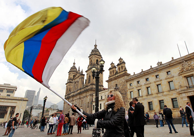 People demonstrate on the street as Colombia's President Juan Manuel Santos and Marxist FARC rebel leader Rodrigo Londono sign a new peace accord in Bogota