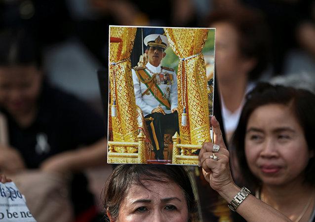 Una mujer con el retrato del nuevo rey de Tailandia