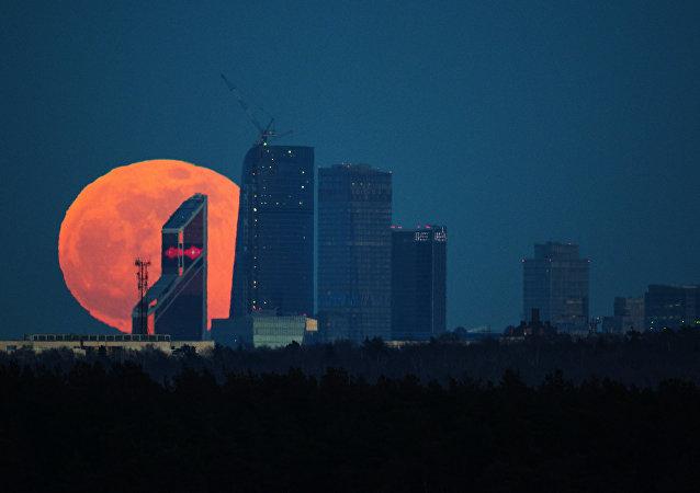 La luna llena detrás de los edificios del centro de negocios Moscow City