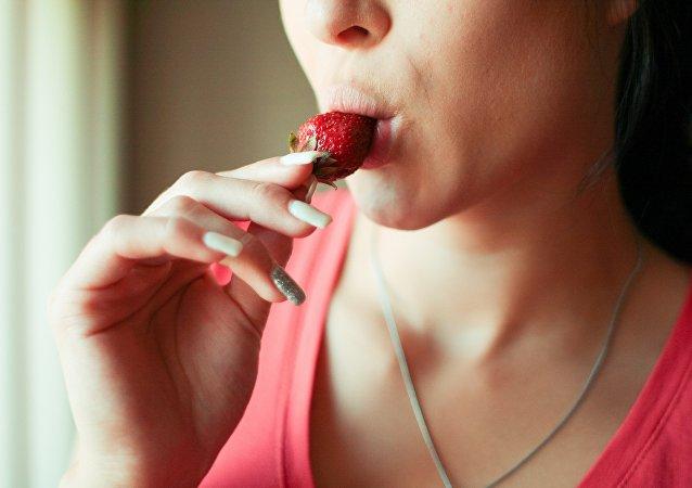 Una mujer comiendo una fresa
