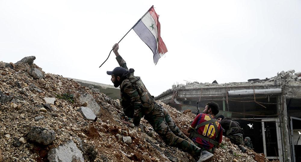Militar sirio emplaza la bandera nacional de Siria durante los combates en Alepo oriental