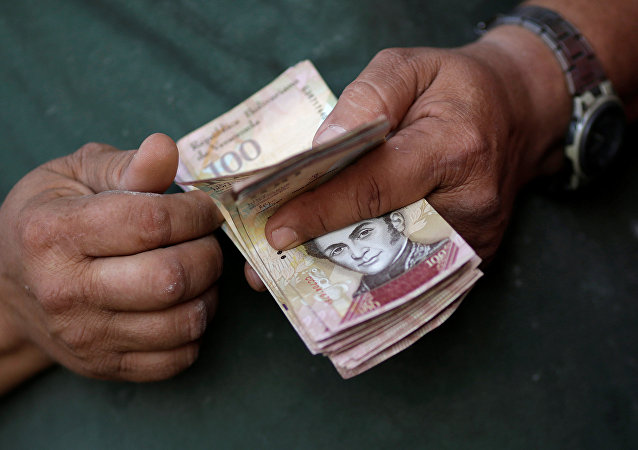 A cashier counts Venezuelan bolivar notes at a street market in downtown Caracas