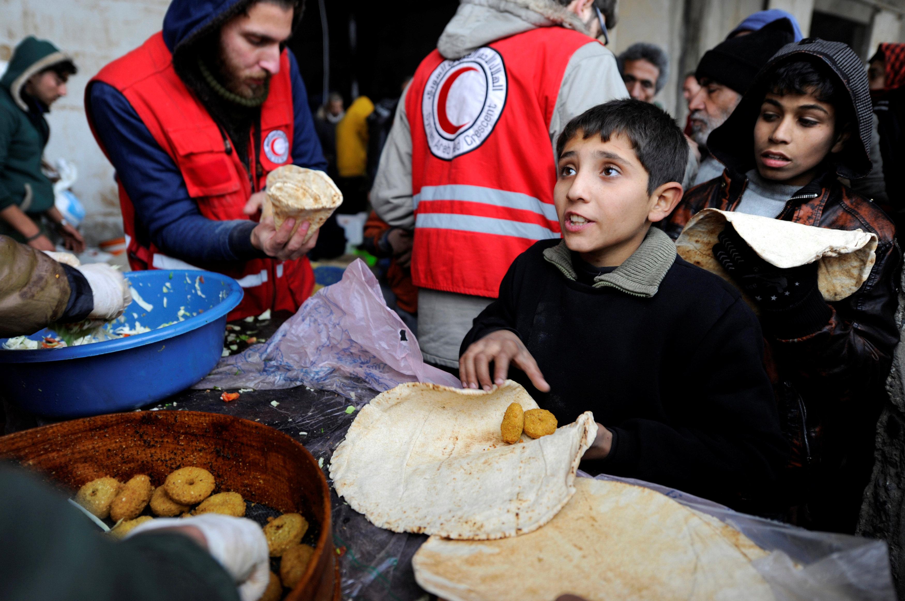 Niños sirios evacuados de las zonas de Alepo controladas por los radicales reciben ayuda en el barrio de Jibreen, controlado por el Gobierno, 30 de noviembre de 2016