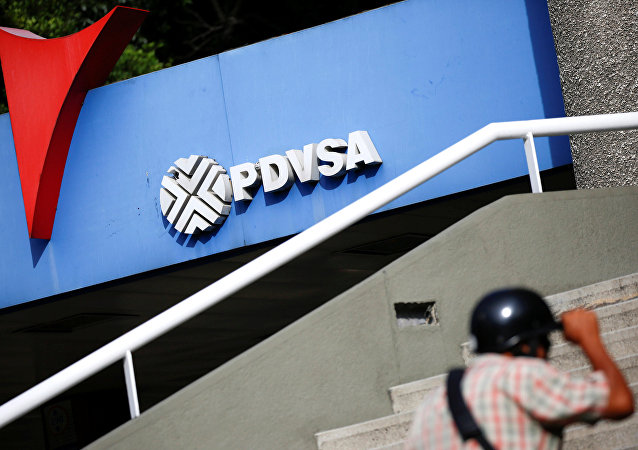 A man walks past a gas station with the logo of the Venezuelan state oil company PDVSA in Caracas, Venezuela December 23, 2016. REUTERS/Carlos Garcia Rawlins