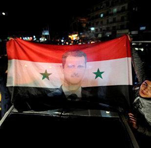 La bandera de Siria con el retrato de Bashar Asad