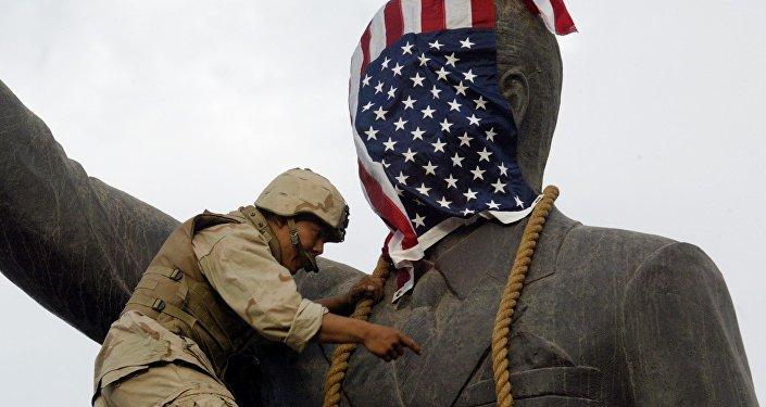 Un soldado estadounidense cubre la estatua de Sadam Husein con la bandera de EEUU