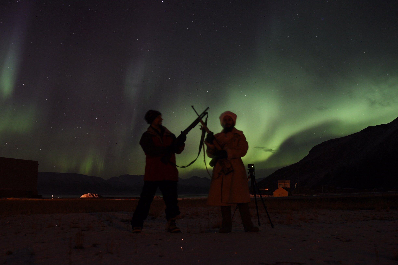 Sasha con su colega-guía con aurora boreal de fondo