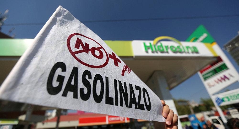 Un hombre sostiene un letrero durante una manifestación contra el aumento de los precios de la gasolina en Ciudad de México