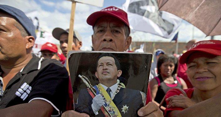 Un chavista en Venezuela con una fotografía de Hugo Chávez