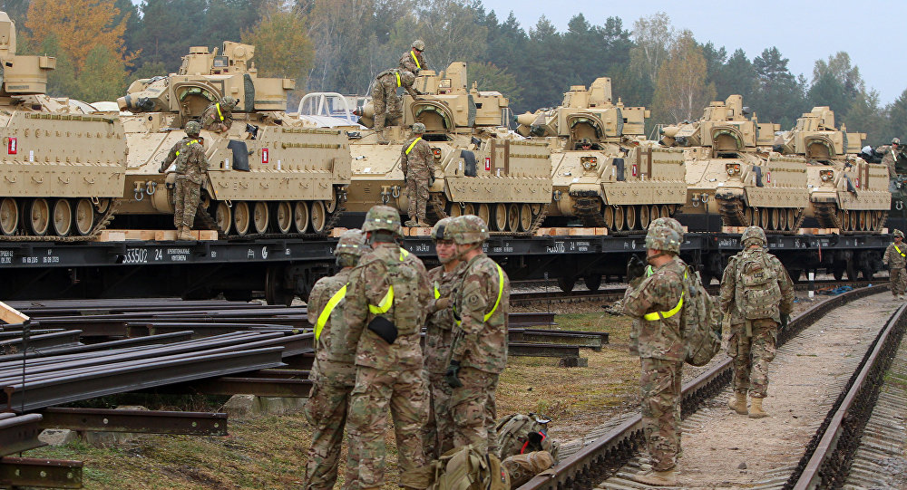 Members of the US Army 1st Brigade, 1st Cavalry Division, unload heavy combat equipment including Bradley Fighting Vehicles at the railway station near the Rukla military base in Lithuania, on October 4, 2014