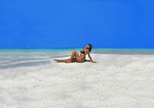 Una mujer toma sol en la playa