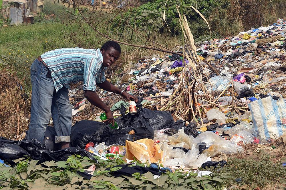 Un residente de una ciudad de Nigeria hurga en la basura en busca de sobras