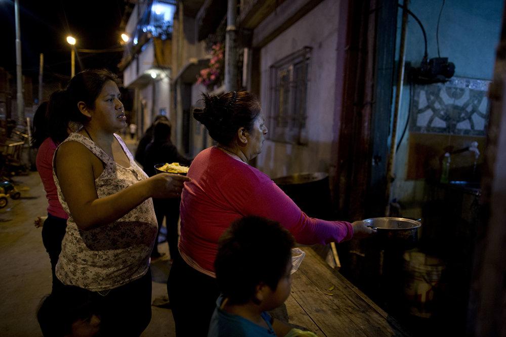 Mujeres en Buenos Aires hacen cola por un almuerzo gratuito para sus familias