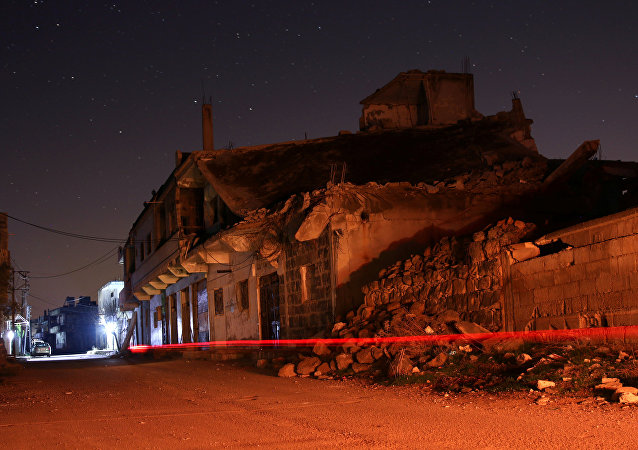 Edificios dañados se ven por la noche en la ciudad rebelde de Dael