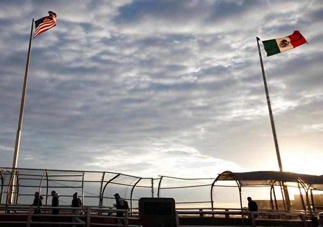Banderas de EEUU y México en la frontera entre dos países
