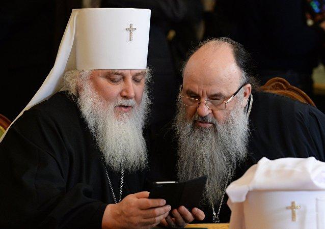 Los clérigos ortodoxos con un teléfono móvil