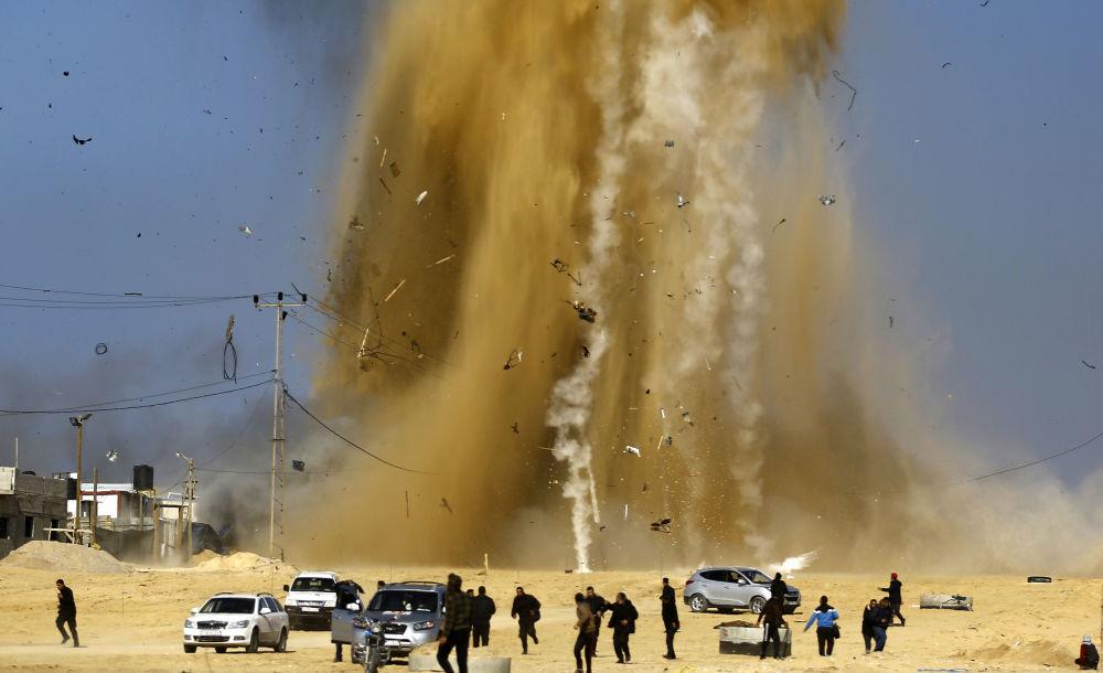 Palestinos corren hacia un escondite después de un ataque aéreo contra el punto de control de Hamas en la parte norte de la Franja de Gaza