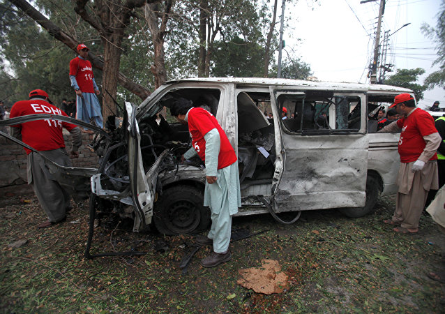 Volunteers search for remains in a vehicle at the scene of a bomb attack in Peshawar, Pakistan