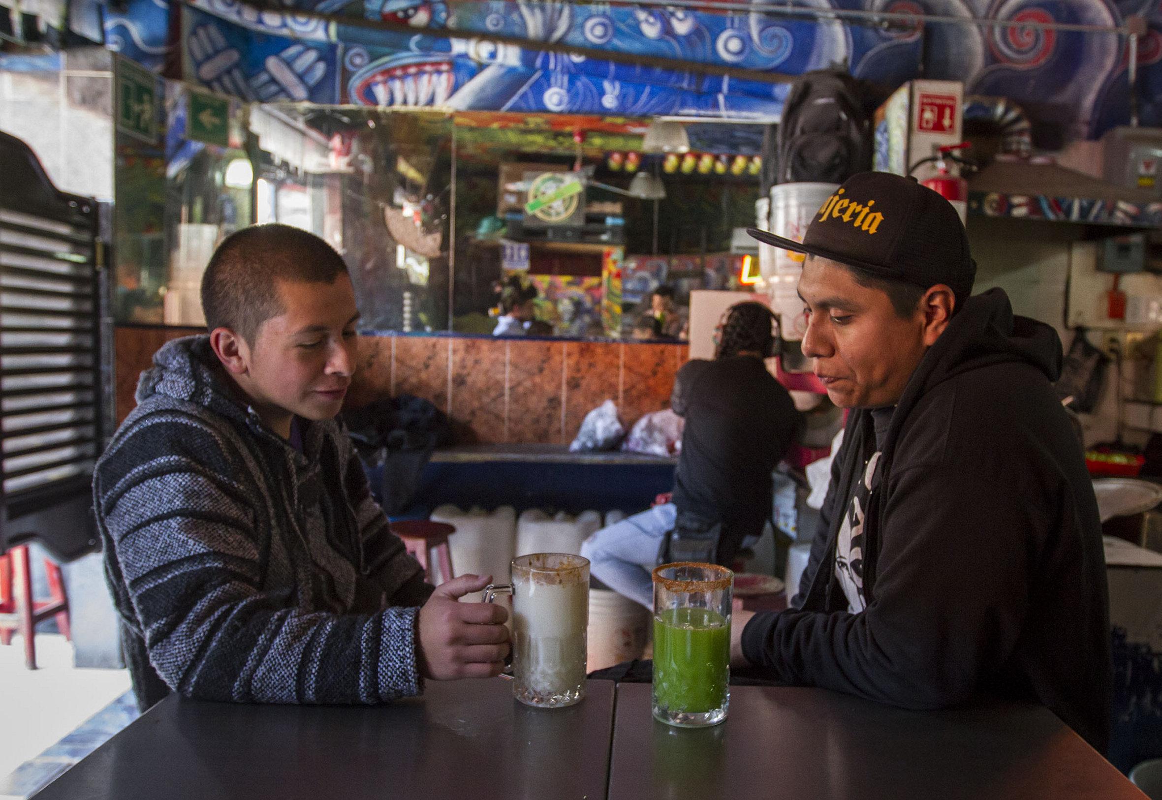 Dos hombres beben pulque
