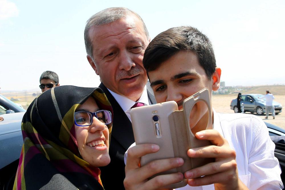 El presidente turco, Recep Tayyip Erdogan, se hace una autofoto con unos transeúntes durante una visita a la sede de la Policía en Ankara