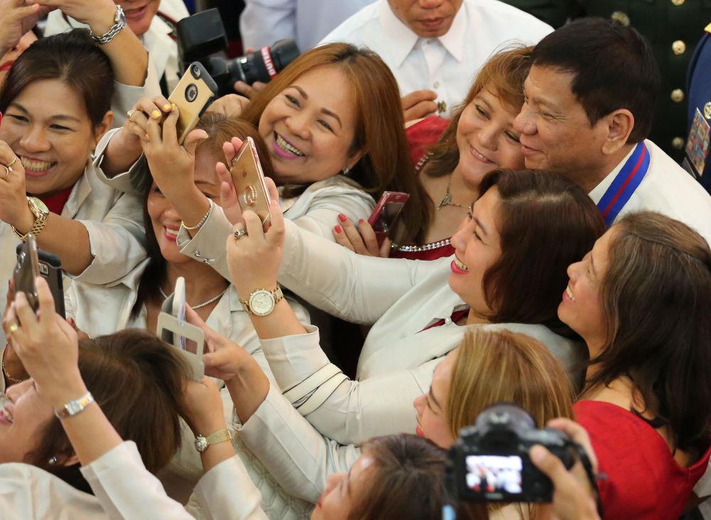 Varias mujeres se toman un 'selfi' con el presidente de Filipinas, Rodrigo Duterte, en la ceremonia de nombramiento de la Jefatura de la Policía Nacional del país asiático