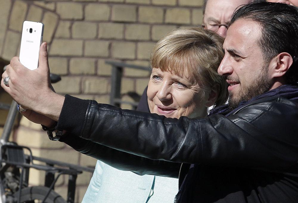 La canciller alemana, Angela Merkel, fue fotografiada con un refugiado durante su visita a los campamentos de migrantes en Berlín