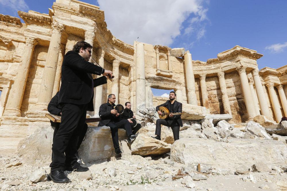 Músicos sirios tocan en el sitio del anfiteatro romano en la antigua ciudad de Palmira, Siria, el cual fue en parte destruido por los terroristas