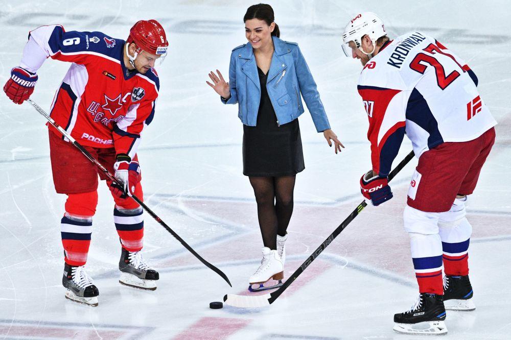 El jugador del club de hockey CSKA Denis Denísov, la campeona olímpica de patinaje artístico Adelina Sótnikova y el jugador del club de hockey Lokomotiv Staffan Kronwall antes del partido de los cuartos de final de los playoffs de la Copa Gagarin