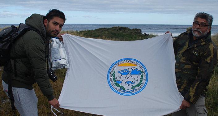 El excombatiente de la Guerra de Malvinas Armando González y su hijo Martín sostienen una bandera