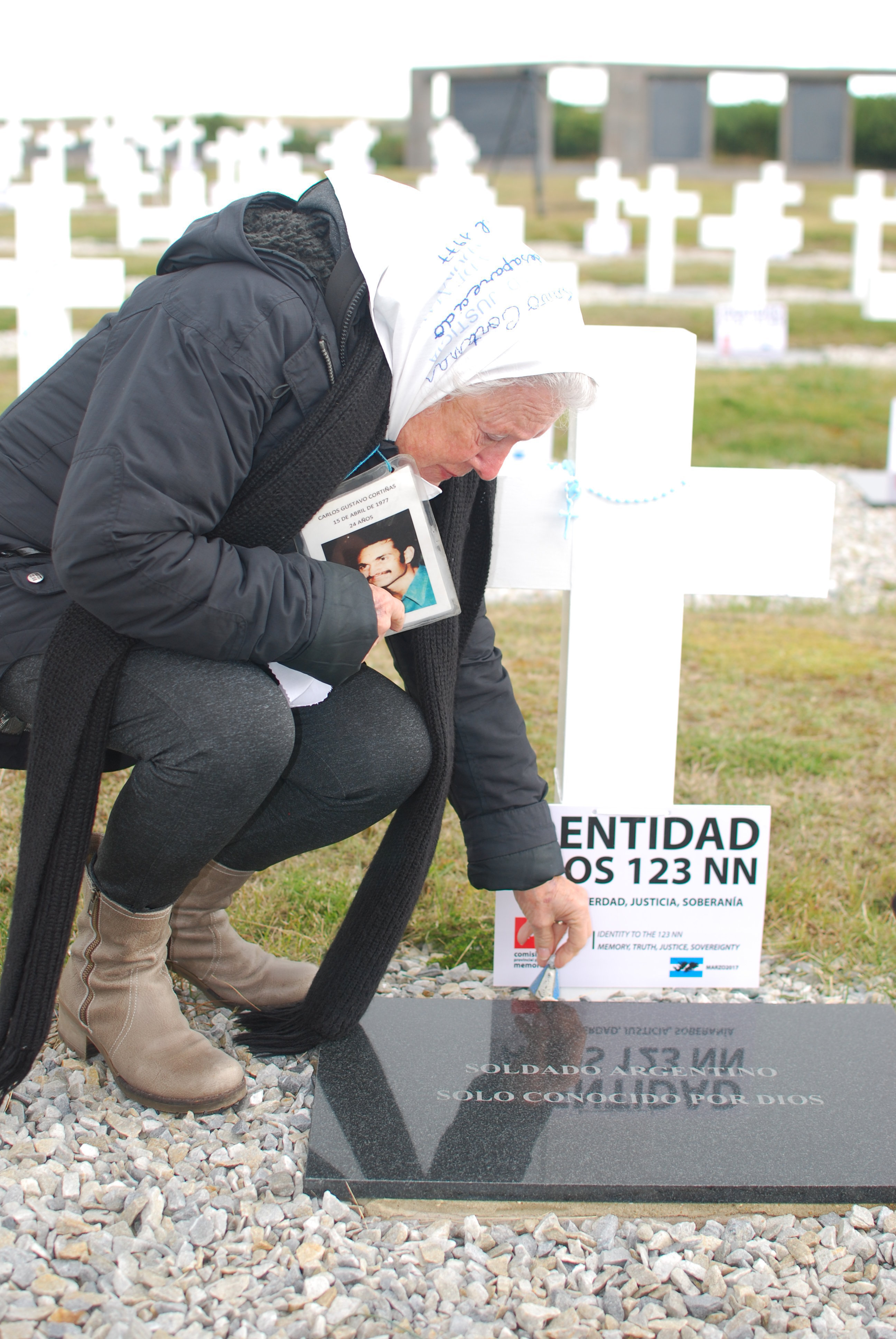 Nora Cortiñas coloca un cartel en una tumba de un soldado desconocido en el Cementerio de Darwin