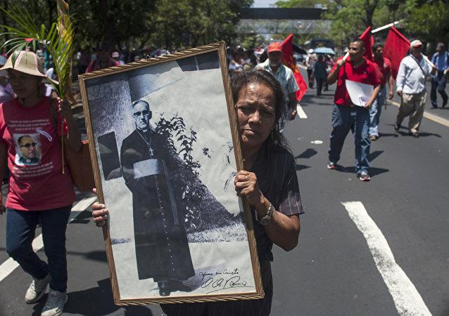 Una mujer sostiene retrato del Monseñor Óscar Romero asesinado en la década de los 80