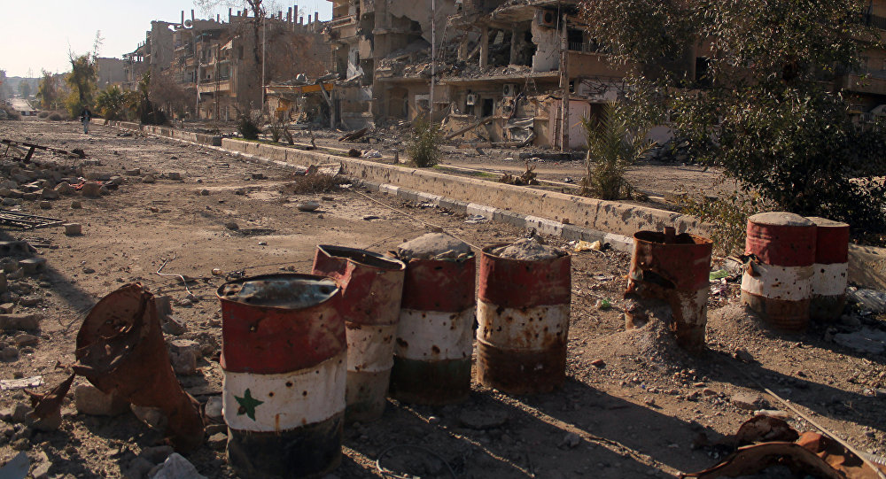 Barrels painted in the colours of the Syrian flag in the eastern town of Deir Ezzor