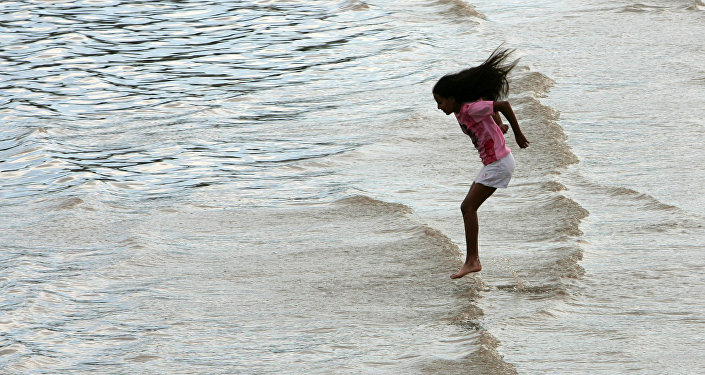 A young girl jumps in the water to cool off during a hot summer day in Buenos Aires' Rio de la Plata