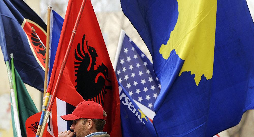 Un hombre vendiendo banderas de Kosovo y Albania
