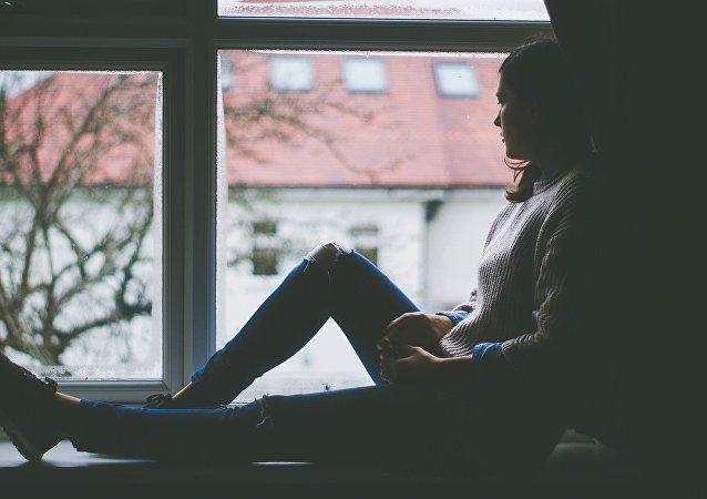 Una mujer pensativa mira por la ventana (imagen referencial)