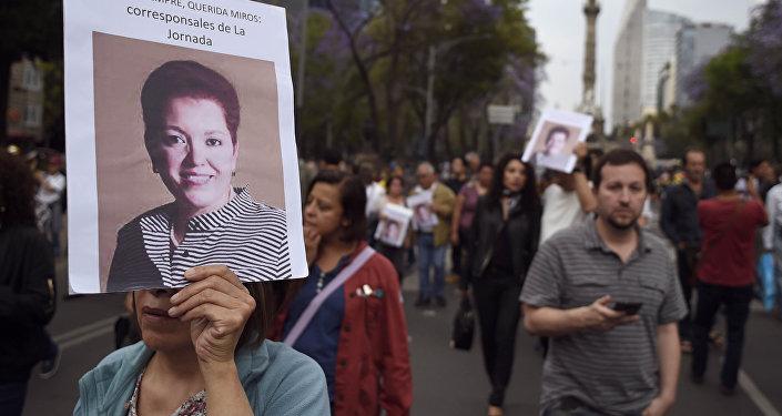 Una mujer con la foto de la periodista Miroslava Breach