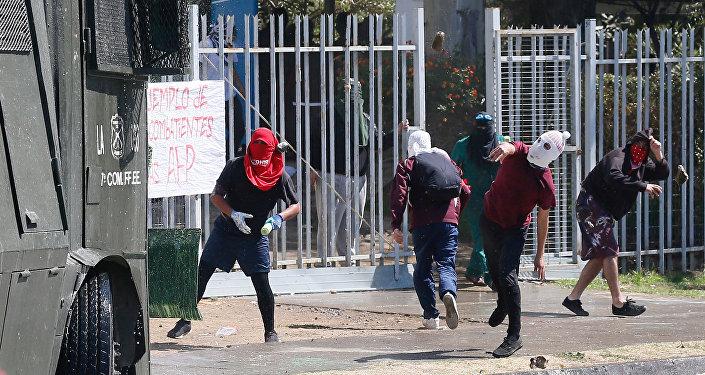 Manifesantes tiran piedras contra los policías durante el Día del Joven Combatiente en Chile