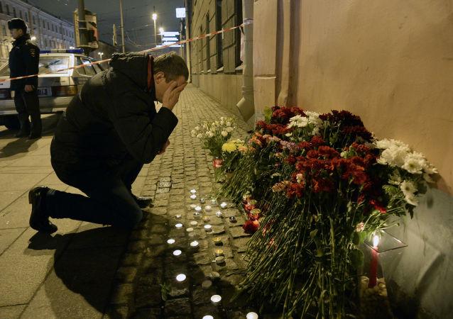 Un hombre poniendo flores en homenaje de las víctimas de la explosión en San Petersburgo