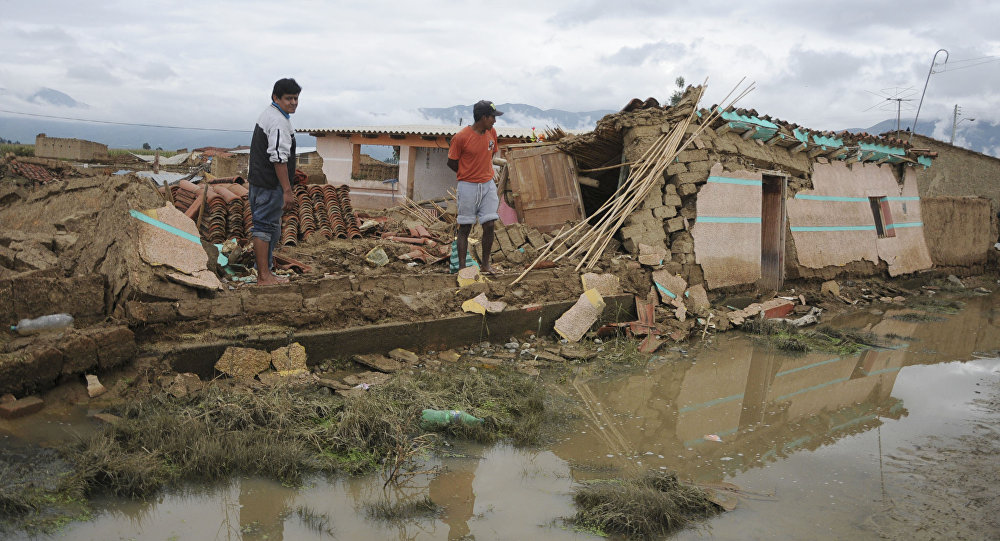Two men look at collapsed houses after a flood in Churusi-Punata in Cochabamba, Bolivia, Friday, Feb. 7, 2014. The latest report released by Bolivia's Ministry of Defense said the storms plaguing Bolivia since last September has left a momentary balance of dozens of deaths and thousands of families evacuated from their homes.
