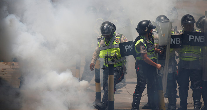 Police stand amidst tear gas during clashes with demonstrators at an opposition rally in Caracas, Venezuela