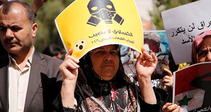 Una manifestante contraria al ataque aéreo de EEUU en Siria porta una pancarta en la que puede leerse: ¿Los productos químicos no afectan a los Cascos Blancos?