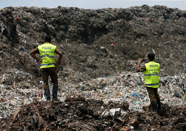 La policía de Sri Lanka frente a una montaña de basura en Meethotamulla, Colombo