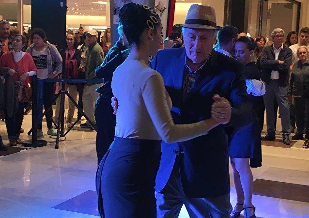 Personas bailan tango en un centro comercial de Montevideo