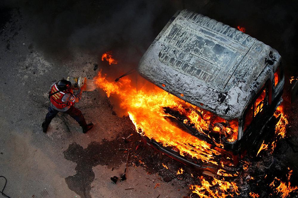Un bombero extingue el fuego de un vehículo en llamas durante una manifestación contra el presidente venezolano, Nicolás Maduro