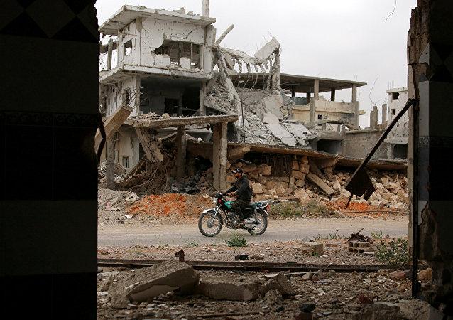 Un hombre monta una motocicleta cerca de los edificios dañados en la zona rebelde en Siria