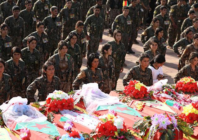 Combatientes de las Unidades de Protección del Pueblo Kurdo (YPG) se reúnen cerca de los ataúdes de otros combatientes durante su funeral