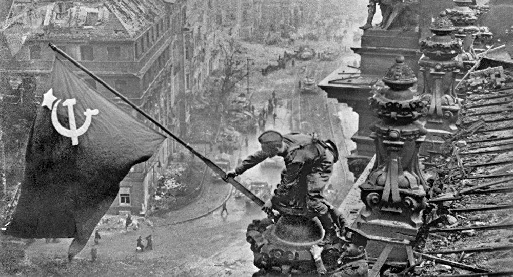 Soldado del Ejército Rojo enarbolando la bandera de la victoria sobre el Reichstag