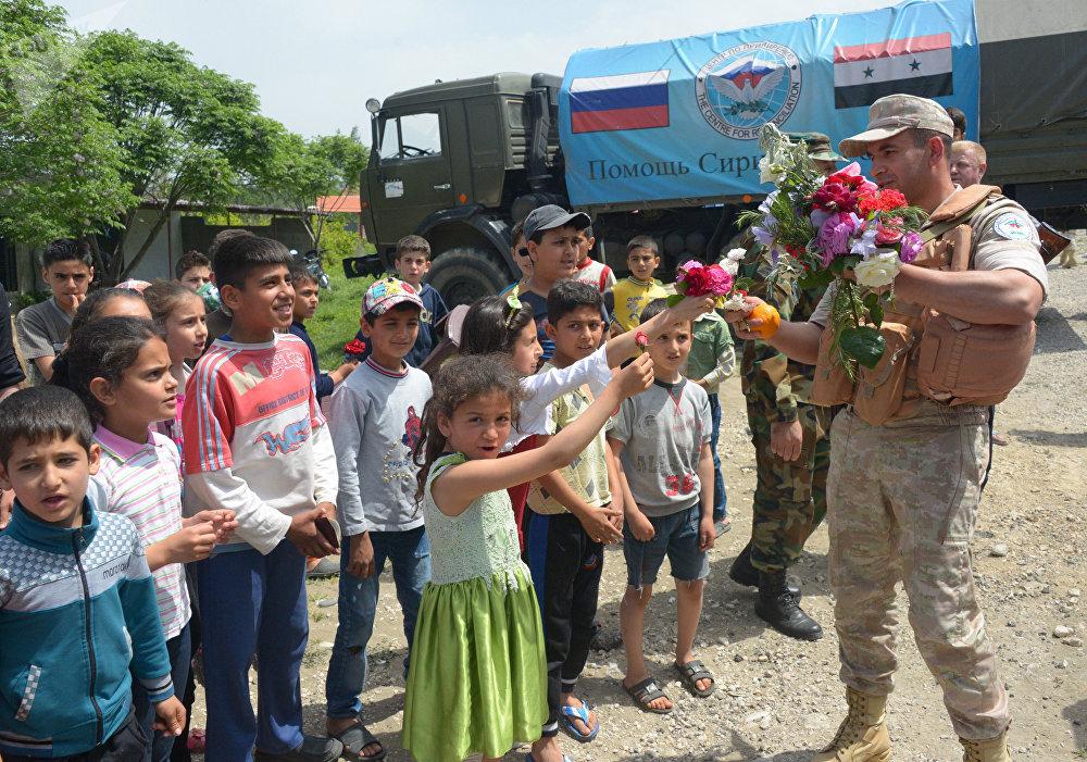 Los habitantes del pueblo sirio de Brabishbo reciben con flores y naranjas a los militares rusos que les llevan ayuda humanitaria.